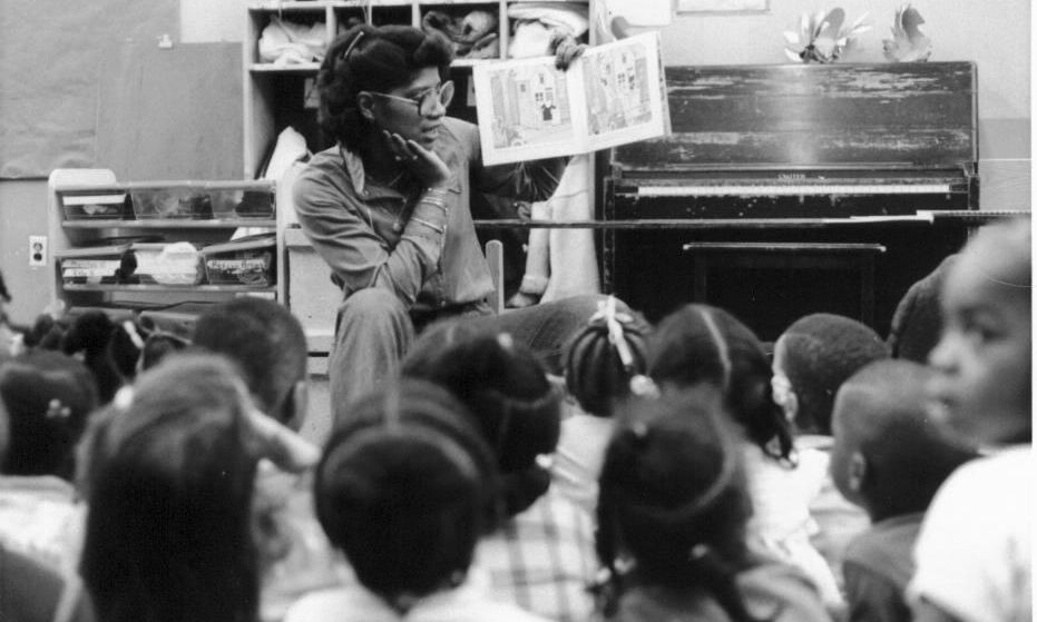 Jesuit Volunteer 1979 reads to students while teaching at their JV placement site in Newark.