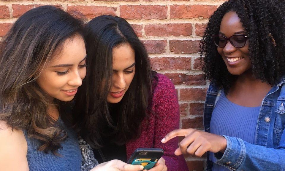 Brooklyn Jesuit Volunteers (2017-18) browse through social media on their phones.