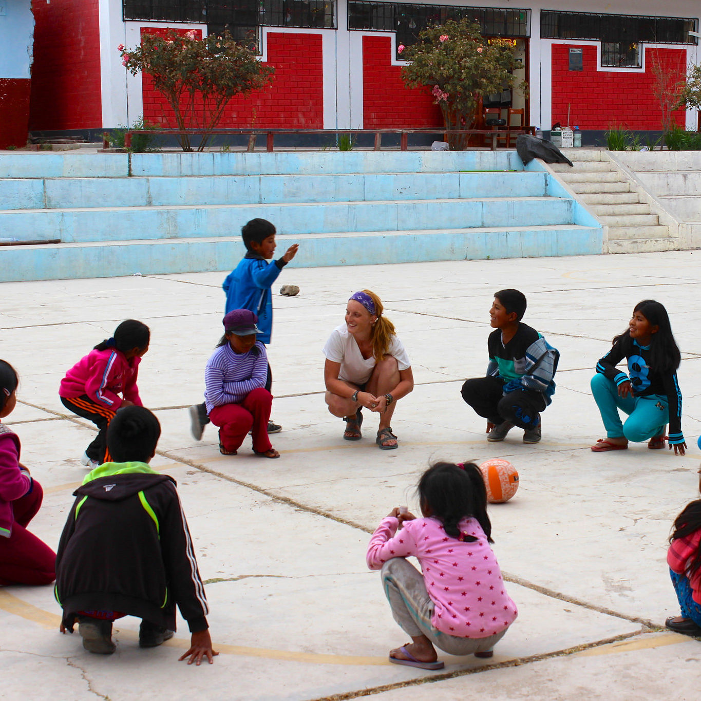 "Jesuit Volunteer plays ""pato, pato, neto"" or duck, duck, goose with young children. (2016)"