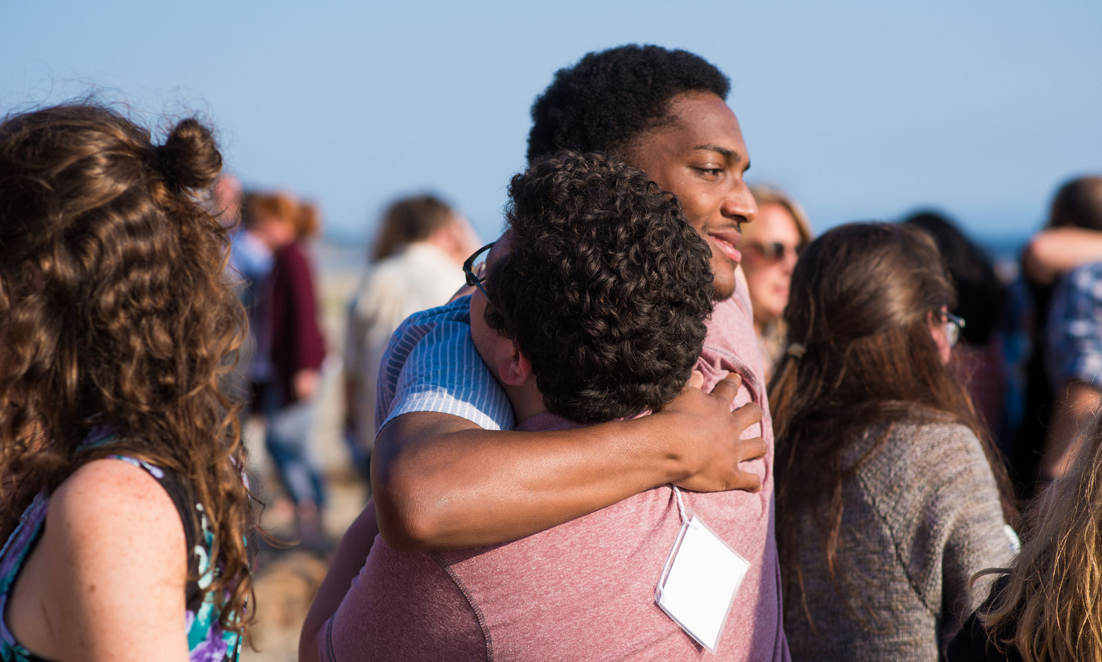 Nico Moore and Taylor Caron - Casa Martin Luther King Jr., San Francisco, CA embrace in a sign of peace at commissioning mass. (2017)